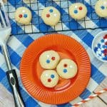 patriotic sugar cookies on red plate and baking rake with spatula and blue tablecloth