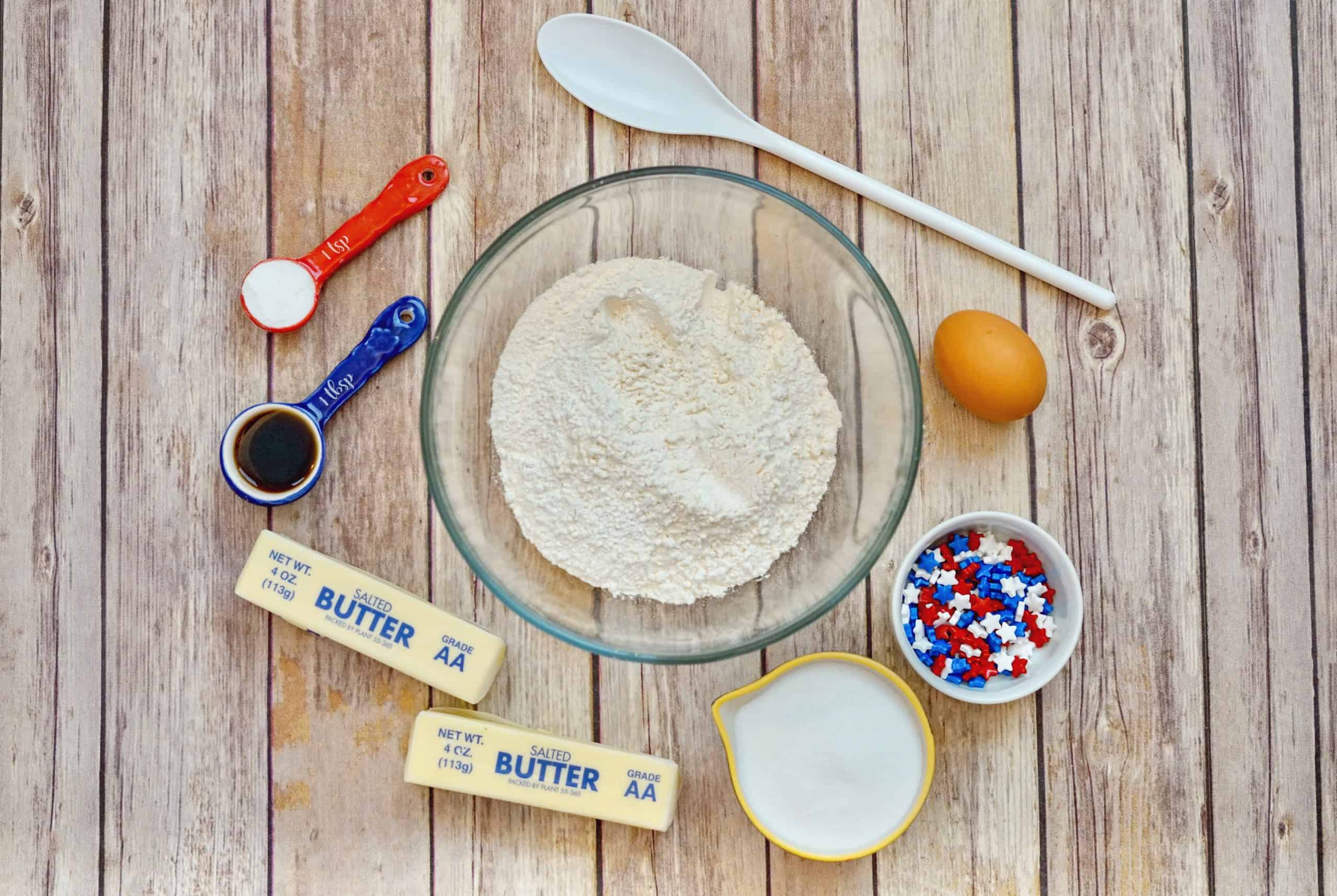 ingredients for making patriotic sugar cookies on wooden table