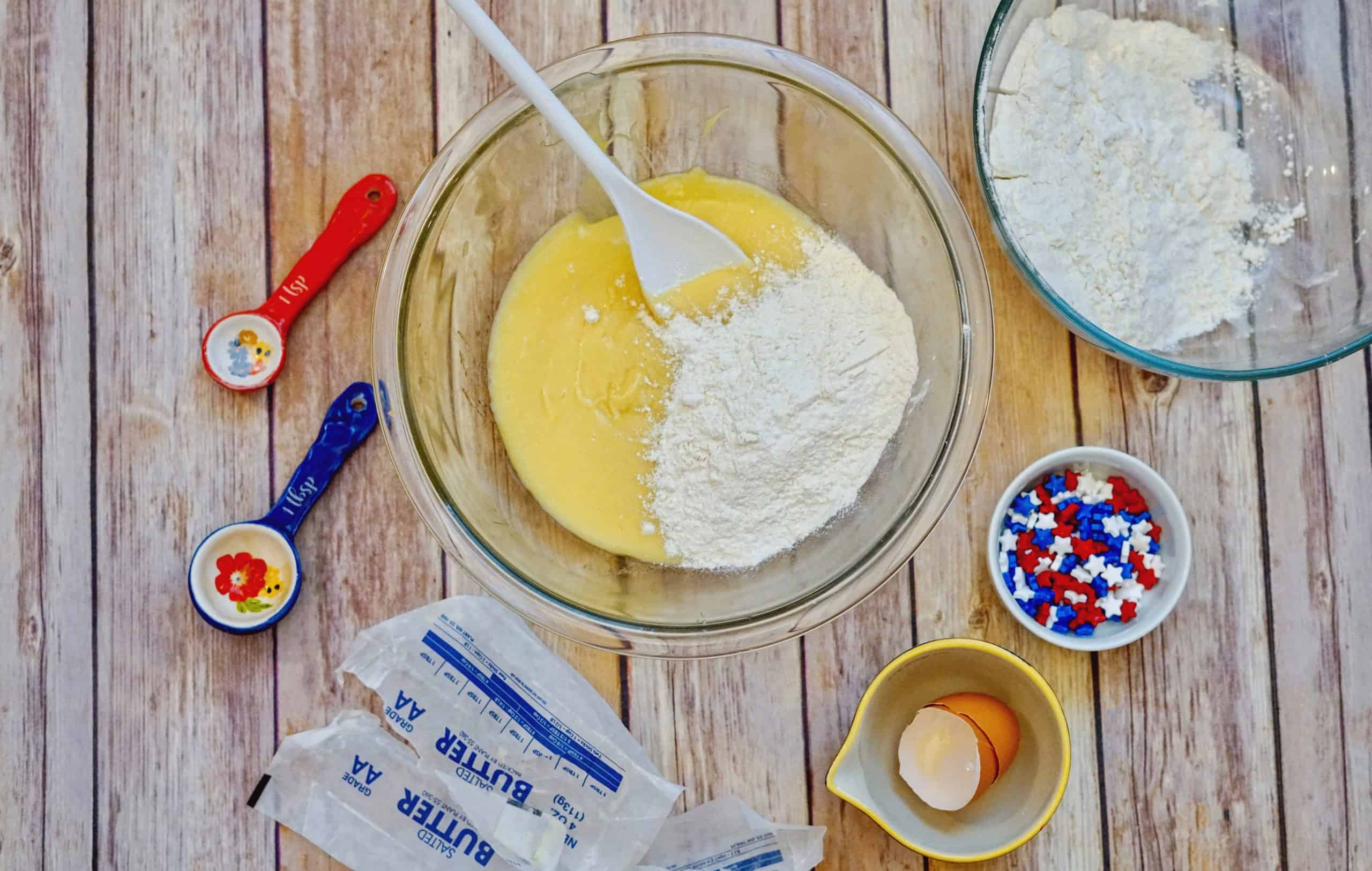 ingredients for patriotic sugar cookies being mixed in bowl