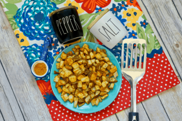air fried cajun potatoes on plate with spatula and other kitchen decor