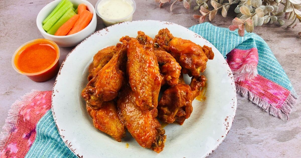 sauced air fryer wings on a plate with dipping sauce and sides
