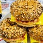 three gluten free bagel sandwiches on a plate