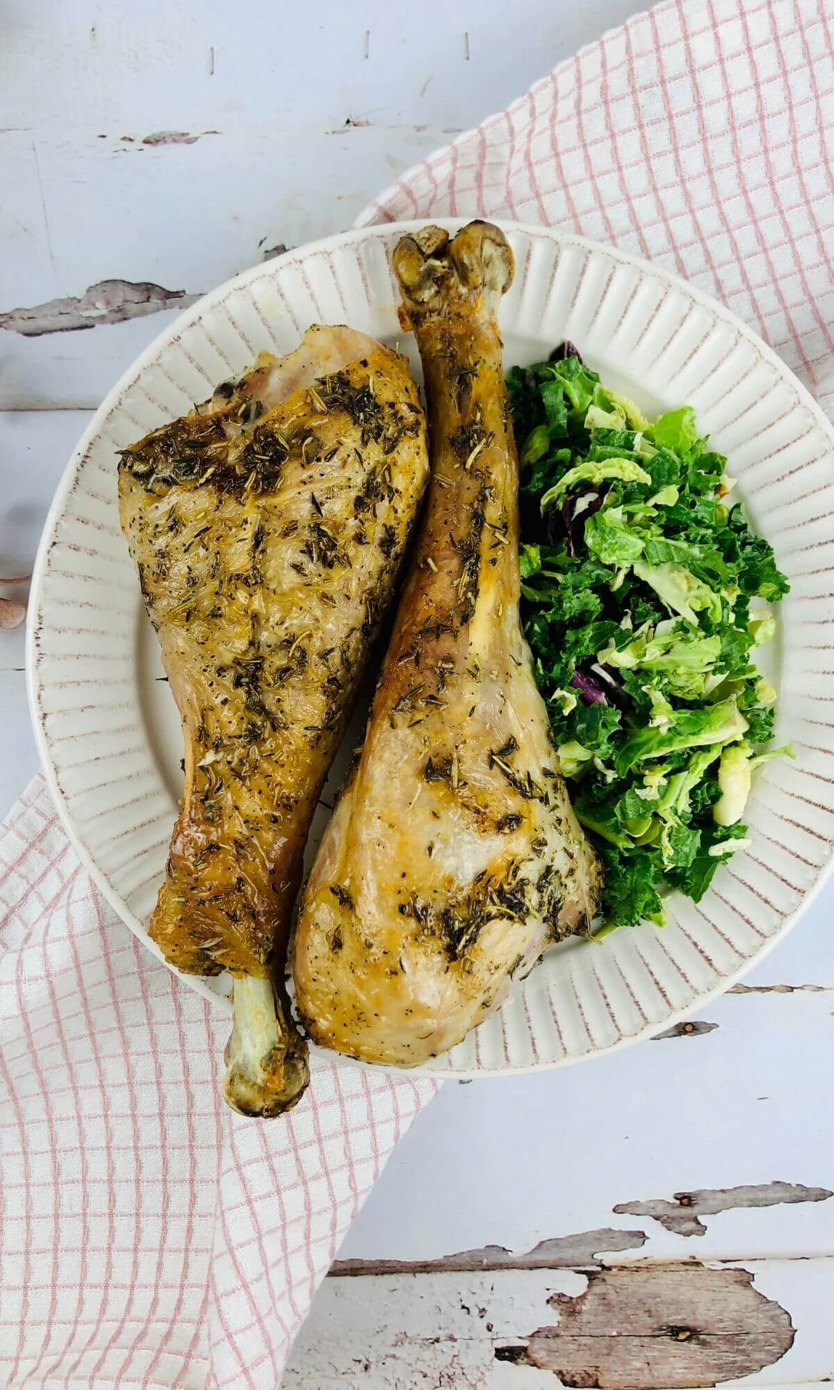 cooked air fryer turkey legs on a plate with garnish